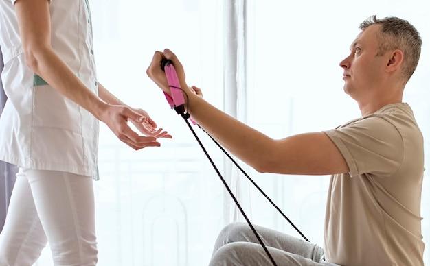 Vrouwelijke therapeut die fysiotherapie ondergaat met mannelijke patiënt Gratis Foto