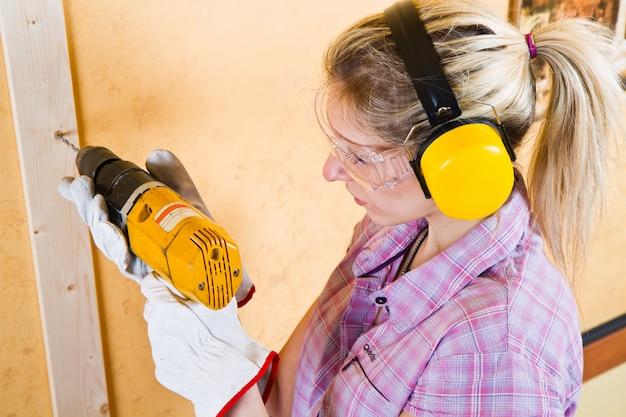 Vrouwelijke timmerman aan het werk met behulp van hand boren machine Premium Foto