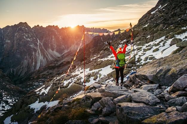 Vrouwelijke toerist die bij hoge tatra bij gouden zonsondergang, slowakije wandelen Premium Foto
