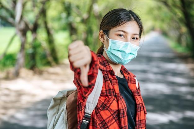 Vrouwelijke toerist die een rugzak en duimen op de weg draagt. Gratis Foto