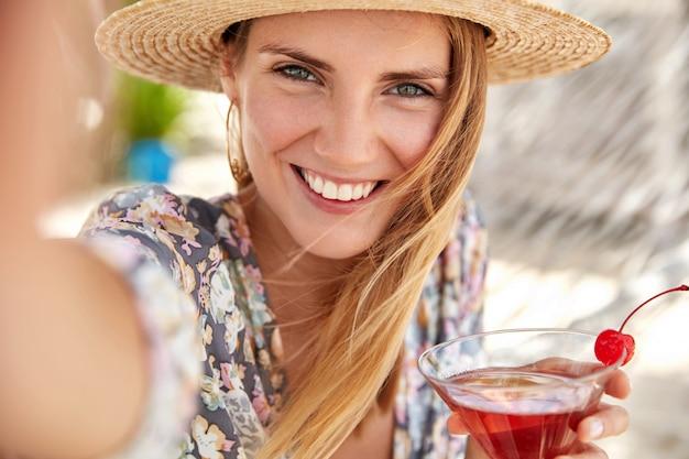 Vrouwelijke toerist geniet van zomervakanties, drinkt lekkere koude cocktail versierd met kersen, maakt foto van zichzelf of selfie met onherkenbaar apparaat. zomertoerisme, levensstijl en rustconcept Gratis Foto