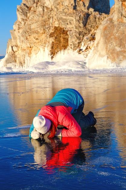 Vrouwelijke toerist kijkt door transparant ijs Premium Foto