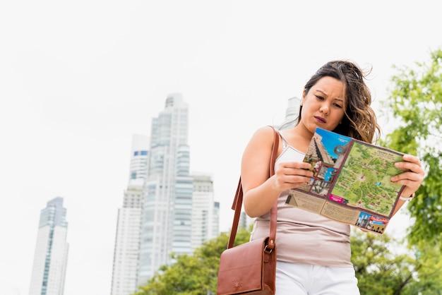 Vrouwelijke toerist met zak op schouders die kaart in de stad onderzoeken Gratis Foto