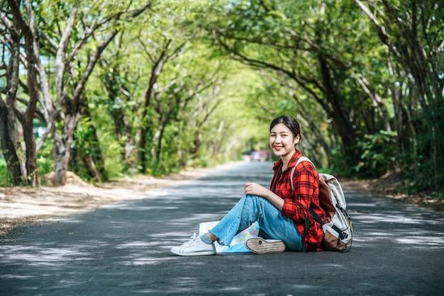 Vrouwelijke toeristen die rugzak dragen en op de weg zitten. Gratis Foto