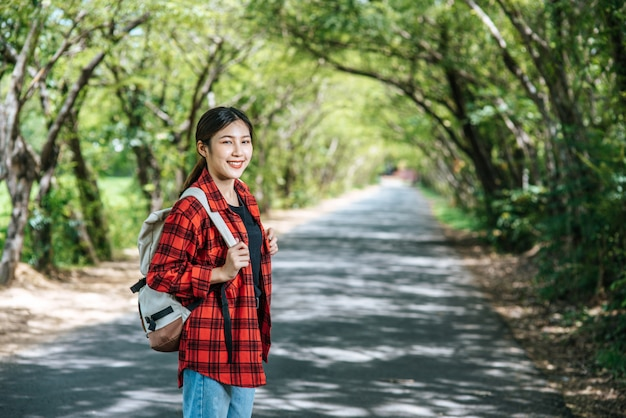 Vrouwelijke toeristen dragen een rugzak en staan op straat. Gratis Foto