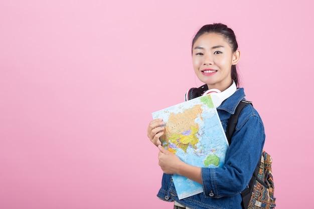 Vrouwelijke toeristen in de studio op een roze achtergrond. Gratis Foto