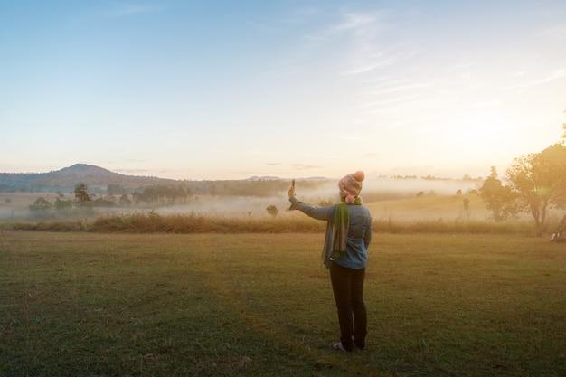Vrouwelijke toeristen nemen een foto met smartphone tijdens dramatische zonsopgang op mistige zomerochtend, concept van outdoor camping avontuur Premium Foto