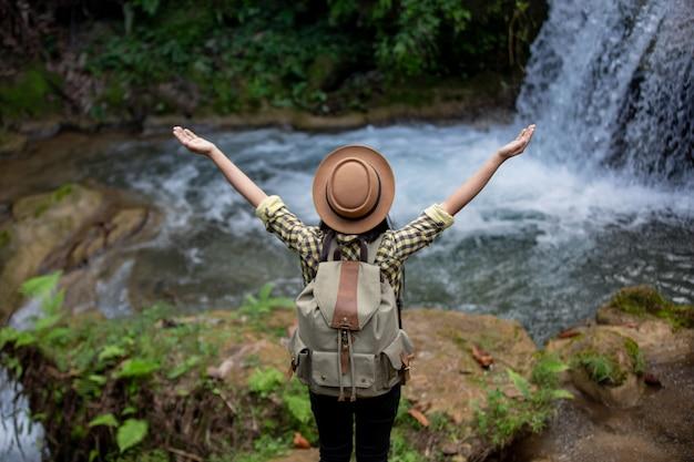 Vrouwelijke toeristen zijn blij en verfrist bij de waterval. Gratis Foto