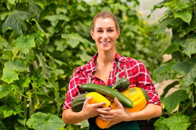 Vrouwelijke tuinman in markttuin of kinderdagverblijf Premium Foto