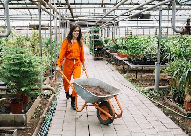Vrouwelijke tuinman in workwear duwende kruiwagen met grond in serre Gratis Foto