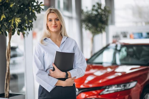 Vrouwelijke verkoper in een autoshowroom Gratis Foto