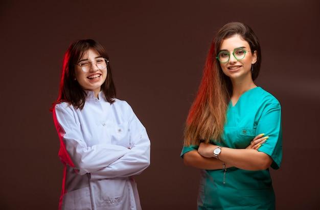 Vrouwelijke verpleegster en arts zien er professioneel uit en glimlachen. Gratis Foto