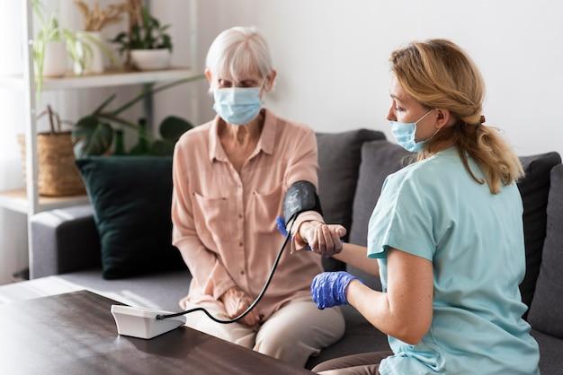 Vrouwelijke verpleegster met medisch masker met behulp van een bloeddrukmeter op oudere vrouw Premium Foto