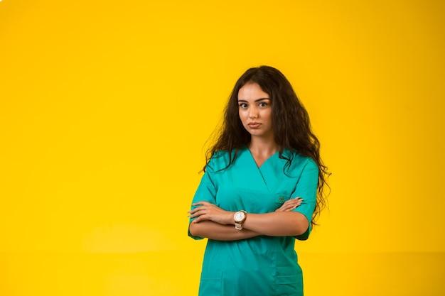 Vrouwelijke verpleegster sluitende handen en ziet er twijfelachtig uit. Gratis Foto