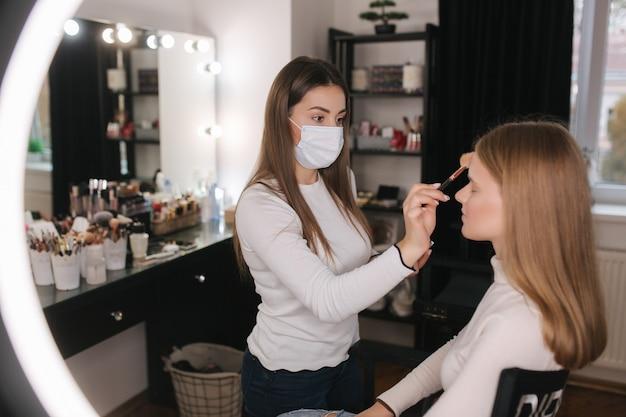 Vrouwelijke visagist die in de schoonheidssalon werkt tijdens quarantaine Premium Foto