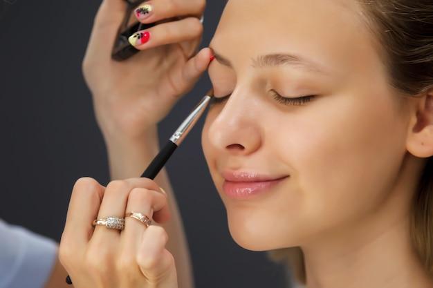 Vrouwelijke visagist maakt leuke mooie jonge vrouw in de schoonheidssalon. klantenservice in binnensalon om een geweldig beeld te creëren. werk make-up maken wizard. concept schoonheidstevredenheid Premium Foto