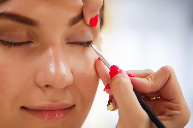 Vrouwelijke visagist maakt leuke mooie jonge vrouw in de schoonheidssalon. Premium Foto