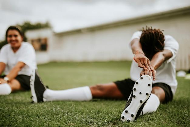 Vrouwelijke voetbal speler die zich uitstrekt voor een wedstrijd Premium Foto