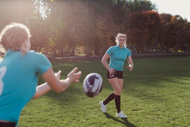 Vrouwelijke voetballer die bal overgaat Gratis Foto