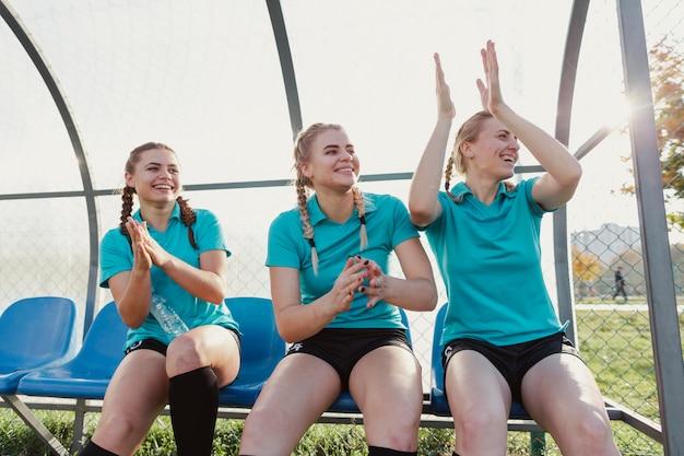 Vrouwelijke voetballers die op een bank en het klappen zitten Gratis Foto