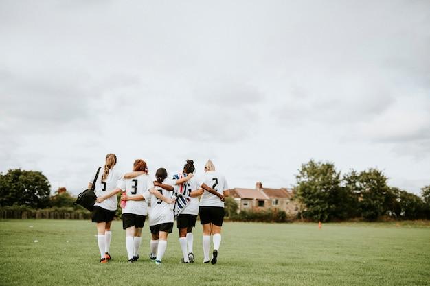 Vrouwelijke voetbalspelers die samen kruipen en lopen Premium Foto