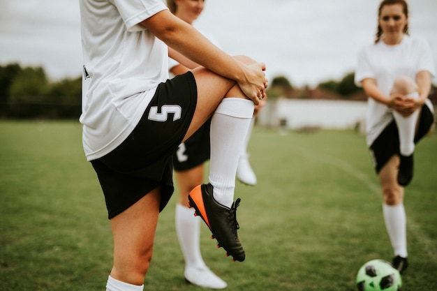 Vrouwelijke voetbalteam spelers die pre-spel uitrekken Premium Foto
