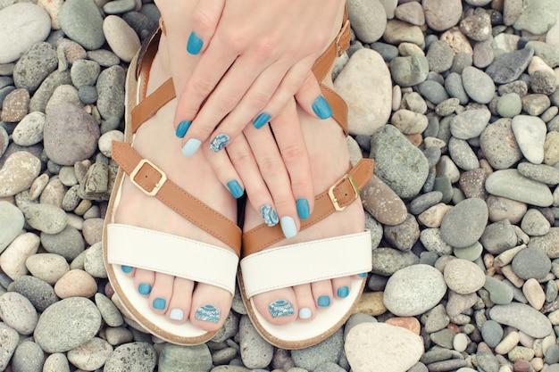 Vrouwelijke voeten in sandalen en handen met een blauwe manicure op kiezelstenen. bovenaanzicht Premium Foto