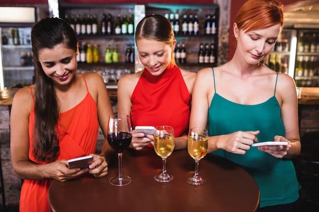 Vrouwelijke vrienden die mobiele telefoon met behulp van terwijl het genieten van van wijn Premium Foto