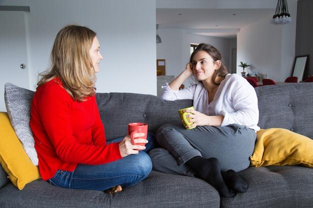 Vrouwelijke vrienden die over kop van koffie babbelen Gratis Foto