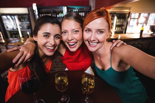 Vrouwelijke vrienden die van wijn in nachtclub genieten Premium Foto