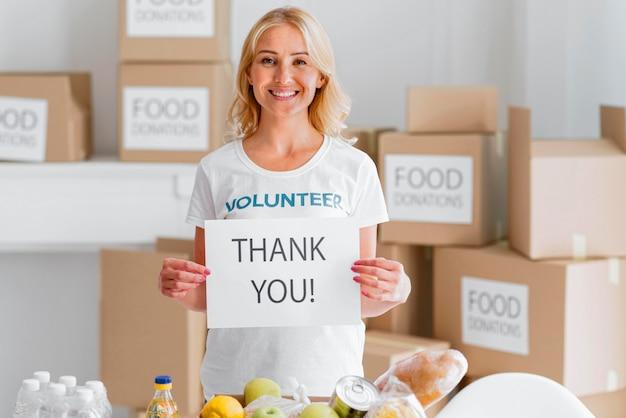 Vrouwelijke vrijwilliger van smiley die je bedankt voor het doneren van voedsel Gratis Foto