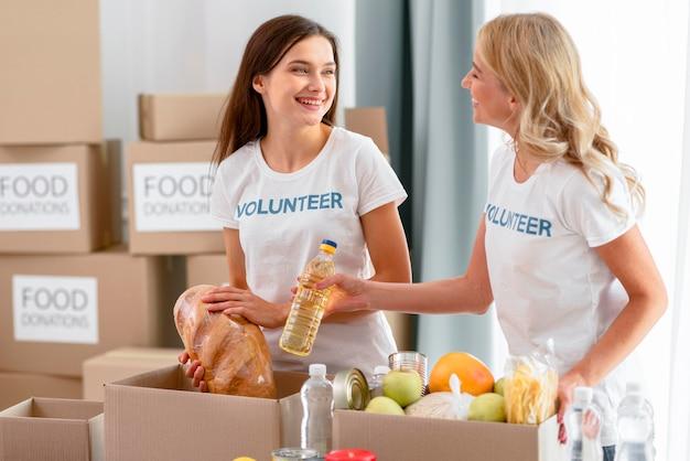 Vrouwelijke vrijwilligers bereiden voedselvoorzieningen voor donaties voor Premium Foto