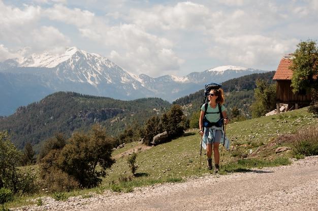 Vrouwelijke wandelaar die dichtbij weg in heuvels reizen Premium Foto