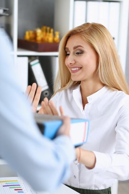 Vrouwelijke werknemer die pak documenten toont Premium Foto