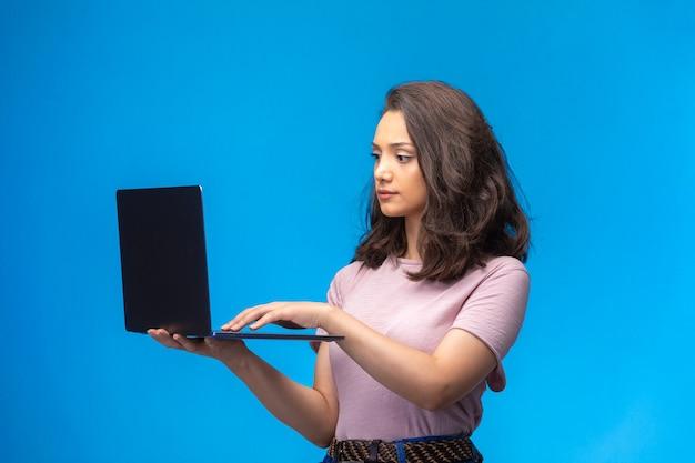 Vrouwelijke werknemer met zwarte laptop die videogesprek heeft. Gratis Foto