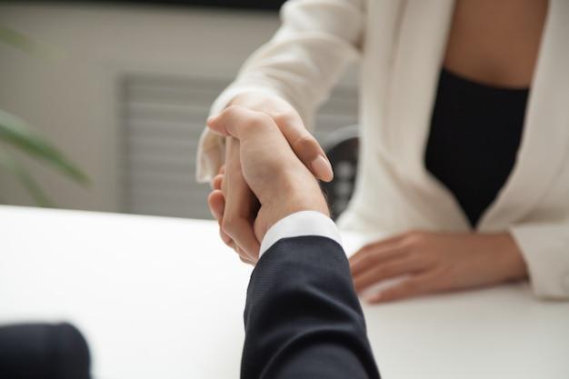 Vrouwelijke werknemersgroet partner met handdruk Gratis Foto