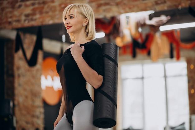 Vrouwelijke yoga-instructeur uitoefenen op de sportschool Gratis Foto