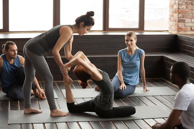 Vrouwelijke yogainstructeur die vrouw helpen die oefening doen bij groepstra Gratis Foto