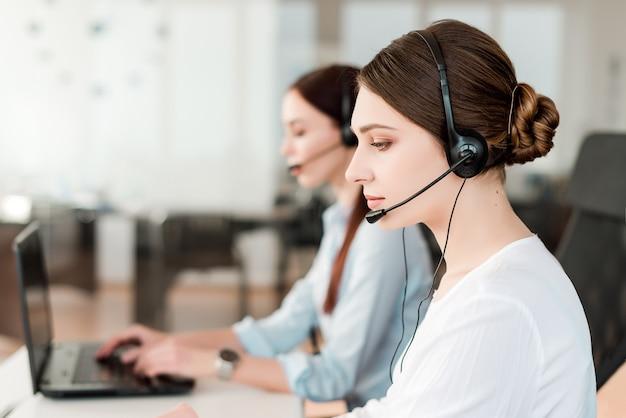 Vrouwen beantwoorden van telefoontjes op kantoor met een head set Premium Foto