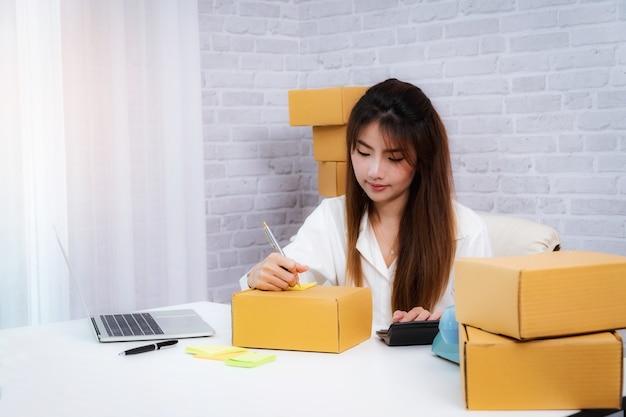 Vrouwen bedrijfseigenaar het schrijven adres op verpakkingsdoos op het werk in huis offce Premium Foto