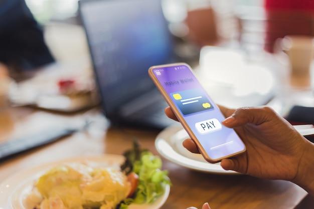 Vrouwen betalen voor eten creditcards gebruiken via mobiele telefoons in restaurants, toekomstige iot- en technologieconcepten Premium Foto