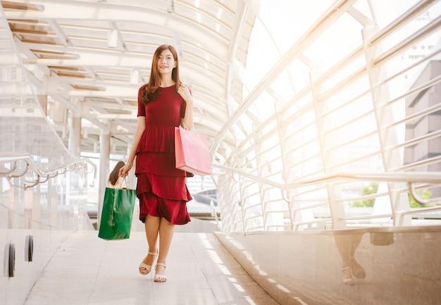 Vrouwen die aan het winkelen, verkoop, consumentisme en mensenconcept lopen. Premium Foto