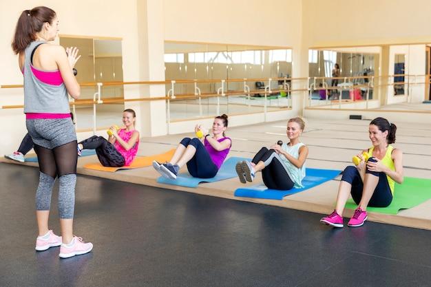 Vrouwen die domooroefeningen doen bij een groepstraining in een fitnessruimte Premium Foto