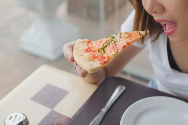 Vrouwen die een heerlijke pizza van margarita in restaurant eten. Premium Foto