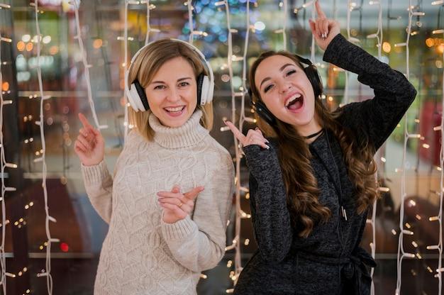 Vrouwen die hoofdtelefoons dragen dichtbij kerstmislichten Gratis Foto