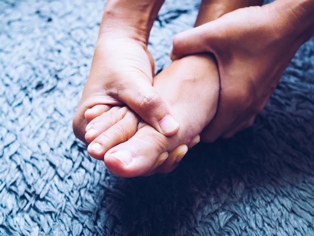 Vrouwen die lijden aan acute voetpijn en met handen masseren op voeten om pijn te verlichten. Premium Foto