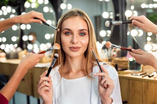 Vrouwen die make-upborstels houden Premium Foto