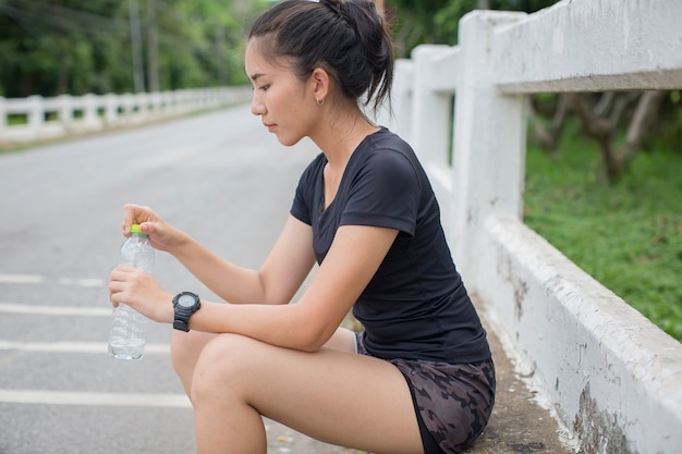 Vrouwen die na het hardlopen water drinken Premium Foto