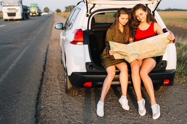 Vrouwen die op witte auto met kaart zitten Gratis Foto