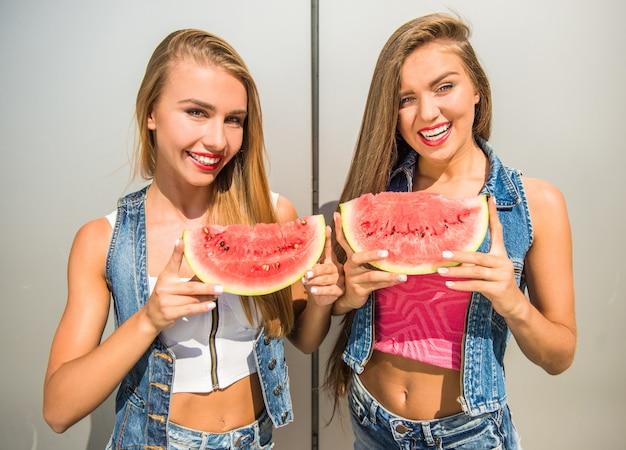 Vrouwen die plakken van watermeloen en het glimlachen houden. Premium Foto